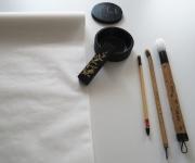 Le bâton d'encre et la pierre à broyer au centre des outils du peintre